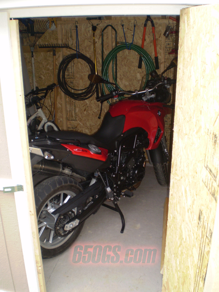 A BMW 650gs motorcycle in a shed.
