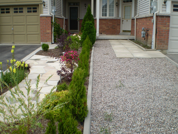 The front yards of two townhomes. One is beautiful and the other is gravel.